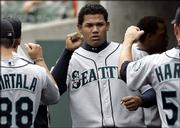 Seattle Mariners pitcher Felix hernandez is congratulated by teammates after being taken out of the game against Detroit. The Tigers won, 3-1, Thursday in Detroit, but the highly touted Hernandez was sharp in his major-league debut.