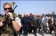Escorted by an armed U.S. soldier, Iraqi Prime Minister Ibrahim Jaafari, center rear, arrives Thursday to attend an Iraqi police graduation ceremony in the southern Iraqi town of Hilla.
