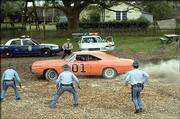"The General Lee races away from the police in a scene from ""The Dukes of Hazzard."" The promotional photo is one of many that obscures the Confederate battle flag painted on top of the stars&squot; Dodge Charger."