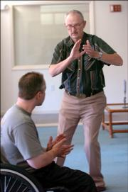 Brower Burchill, right, works on his stance as he creates the bird gesture while tai chi instructor Steve Carrier goes through exercises with a class of elderly pupils.