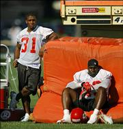 Kansas City running back Priest Holmes, left, takes off morning practice, as he has done throughout preseason training camp. Holmes watched Saturday's practice in River Falls, Wis., with fullback Tony Richardson.