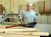 Calvin Ledbetter shows off a nearly finished bat. A block of maple rests on the table, while another bat being turned rests in the lathe in the background.