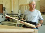 Calvin Ledbetter, co-owner of Lawrence's Diamond Cabinetry, also makes a line of Diamond bats for minor-league players, including his son Curtis, a Lawrence High product now in the Seattle Mariners' minor-league system. A block of maple, foreground, is turned on a lathe, background, before the brand goes on.