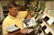 Bill Muggy, general manager and owner of Jayhawk Bookstore, stocks his shelves Friday evening at the store. On Aug. 4, Muggy defended himself in Municipal Court on a city-issued citation for a violation of the city's sign code.
