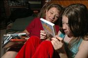 Debby Smith, left, and her 11-year-old daughter, Megan, look through some of the family's favorite DVDs. Smith is a Lawrence PTA member who uses a new Web site to check out movies before she lets her daughter see them. She has recommended the site to the PTA.