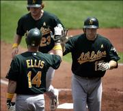 Oakland catcher Adam Melhuse (17) is congratulated by Mark Ellis after Melhuse hit a home run, driving in Bobby Kielty (23), during the second inning. The A's routed the Royals, 11-0, Sunday in Kansas City, Mo.