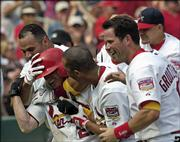 St. Louis's David Eckstein, wearing batting helmet, is mobbed by teammates, from left, Albert Pujols, John Rodriguez and Mark Grudzielanek after hitting a walk-off grand slam against Atlanta. The Cardinals won, 5-3, Sunday in St. Louis.