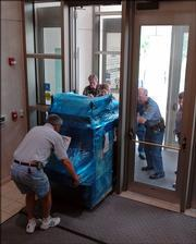Bill Bell, County building maintenance director, foreground, and Douglas County sheriff's deputies deliver a new security screening machine to the Douglas County Judicial and Law Enforcement Center, 111 E. 11th St. The machine, which is similar to an airport conveyor belt scanner for bags, purses and other small items, will be used along with a walk-through scanner for security purposes at the entrance to the center.