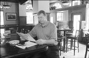 Bobby Douglass, one of the new owners of the Eldridge Hotel, 701 Mass., studies a new menu in the renovated bar area. The former Kansas University and NFL athlete was among alumni who bought the Eldridge, reopening it in May.