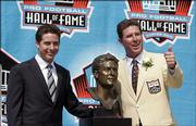 Former Miami Dolphins quarterback Dan Marino poses with his bust after his enshrinement in the Pro Football Hall of Fame. Marino was honored Sunday in Canton, Ohio.