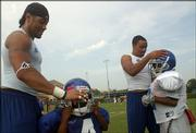 Junior defensive back Kenneth Thompson, left, helps 4-year-old Jevon Thompson with his helmet, while sophomore running back Gary Green, right, helps Malik Thompson, 9, with his lid.
