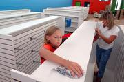 Lauryn Morstorf, 11, Topeka, left, helps Lana Best, right, manager of The Toy Store, clean racks for the store's new location at 936 Mass. The Toy Store, currently at 841 Mass., will make the move into their new 6,000-square-foot building later this month. Morstorf and Best were working in the store Tuesday.