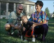 Jeff Krall tries to keep control of the family's energetic dog, Boots, while his wife, Natalie Griego, holds their 1-year-old son, Logan. Griego, a physician, will leave for training for a second tour in Iraq on Friday. It has become increasingly common for service personnel, including doctors, to serve multiple tours. This time, Griego will be away from her family for more than three months.