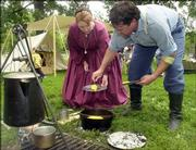 Robbie Walker, Hoyt, puts a piece of cornbread on Arlene Walker's plate, also from Hoyt, during a Civil War re-enactment in August 2004. Events for this year's Civil War on the Western Frontier will take place at the Watkins Community Museum of History, Lawrence Public Library, South Park and other area locations.