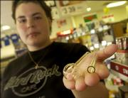 Lawrence resident Jennifer Brown, 21, an employee at the Jayhawk Food Mart, 701 W. Ninth St., has concerns about items such as these glass tubes that are sold at some convenience stores. The tubes, which hold fake roses, can be purchased for little more than a few dollars and are commonly used for smoking crack cocaine.