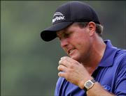 Phil Mickelson reacts to missing a par putt on the ninth green of the final round of the PGA Championship. Mickelson was leading at 4-under par through 13 holes of Sunday's round at Baltusrol Golf Club in Springfield, N.J. Bad weather postponed the conclusion of the round until today.