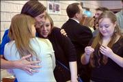 "Carol Wilson, second from left, mother of Kimberly Wilson, is hugged by Carrie Mayhew, left, and Lauren Mayhew, 19, as Rebecca Mayhew, 17, waits at right to extend condolences Monday afternoon at the Free Methodist Church in Lawrence. Kimberly Wilson, 15, died accidentally last Tuesday at her Lawrence home while playing a ""pass out"" game alone."