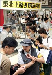 Passengers crowd at Tokyo Station's Shinkansen, or bullet train, ticket counter in Tokyo Tuesday shortly after a magnitude-7.2 earthquake hit the northern Japanese region of Tohoku, halting the train service.