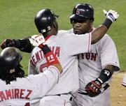 Boston's David Ortiz, right, celebrates with Edgar Renteria, center, and Manny Ramirez after hitting a three-run home run in the 10th inning. Ortiz also hit a solo homer in the ninth. The Red Sox defeated the Tigers, 10-7, in 10 innings Tuesday night in Detroit.