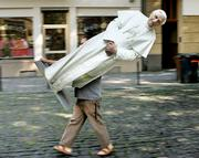 Artist Georg Schmitt carries a cardboard figure showing Pope Benedict XVI in Cologne, western Germany, where hundreds of thousands of pilgrims are gathered for World Youth Day. Pope Benedict XVI will come to the event on Thursday. It is the first foreign trip for the new pope, as well as the first return home for the German-born Catholic leader. Nearly 1 million people are expected for Benedict's open-air Mass on Sunday.