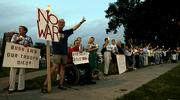 Anti-war protesters wave at passing motorists at a candlelight vigil in support of Cindy Sheehan in Kansas City, Mo. Vigils were held across the country on Wednesday night.