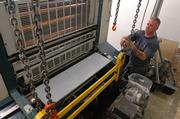 Pete Wright, of Stoner & Co. in Crystal Lake, Ill., moves a section of a new six-color press being installed at Kingston Printing Inc. The new press will enable the printing company to increase its workload.