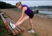 Lawrence resident Shannon Hodges, 26, stretches before a 3-mile run along the Kansas River levee. Hodges completed the San Diego Rock 'n' Roll Marathon in 2002 and the San Francisco Marathon in 2004. Hodges, who runs about 15 miles per week, is considering training for a third marathon.