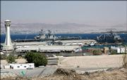 U.S. navy vessels USS Kearsarge, center, an amphibious assault ship, and the USS Ashland, a dock landing ship, sit docked Friday in Aqaba, Jordan, after unknown attackers fired at least three missiles, killing a Jordanian sailor. The U.S. ships left the port following the attack.