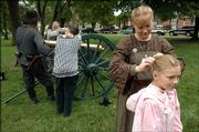 Oleta McCaully, 9, of Kansas City, Mo., has her hair braided by her mom, Carrie Martinez, as more Civil War reenactors hang around a canon at a Civil War encampment at South Park.