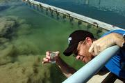 David Brewer, a water quality technician, gathers a water sample from one of the city's water treatment plants.