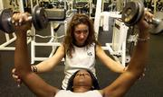 Joanna Clingingsmith, 26, Lawrence, a personal trainer at Lawrence Athletic Club, 3201 Mesa Way, steadies the arms of Wilca Mason, 27, Eudora, as she works out with weights Tuesday afternoon. Many Kansans don't have the same resolve as Mason. A report from the Trust for America's Health says that roughly 23 percent of Kansans are obese, and more than 60 percent of the state's residents are overweight.