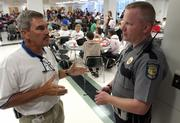 Lawrence High School athletic director Ron Commons, left, talks with school resource officer Jon Barta on Tuesday afternoon in the school cafeteria. As an added security measure for Lawrence junior high and high schools, staff members will soon be issued digital identification cards, which will be used to access doors and computers.
