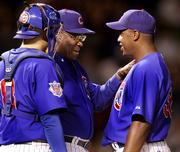 Chicago pitcher Jerome Williams, right, manages a smile as he is taken out of the game by manager Dusty Baker, center, as catcher Michael Barrett looks on. The Cubs defeated the Braves, 10-1, Tuesday night in Chicago.
