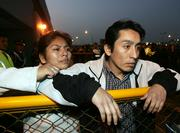 Unidentified relatives of passengers wait for news Tuesday at Jorge Chavez airport in Lima, Peru. A Peruvian airliner carrying 98 people crashed while making an emergency landing on a jungle highway Tuesday, killing at least 37 people and injuring at least 57 others, officials and radio reports said.