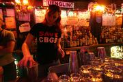 "Wearing a ""Save CBGB"" T-shirt, waitress Jane Keenan mixes a costumer&squot;s drink at the nightclub in New York."
