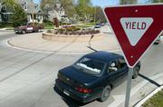 Cars make their way around the roundabout at 19th Street and Barker Avenue. The Lawrence City Commission on Tuesday decided that motorists must go around roundabouts to make left-hand turns, but do not need to make the loop at smaller traffic circles.