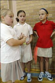 Lawrence Catholic School has introduced a policy requiring students to wear uniforms. The policy offers a wide range of options, including khaki skirts and pants and school brand T-shirts of several colors. From left, St. John school third-graders Makayla Beadleston, Shelby Hill and Bayley Goscha, wear some of the combinations allowed under the new dress code. The three were in gym class Thursday.