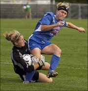 Kansas University forward Caroline Smith, right, runs into a Mississippi player during a game last season. Smith, a senior, is one of three returning All-Americans on the Jayhawks' soccer squad in 2005. KU will begin its season at 2 p.m. today with a game against Michigan at Hummer Sports Park in Topeka.