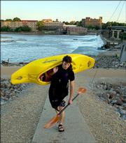 A photo similar to this, showing Kevin Burke carrying his kayak on the north side of the Kansas River, appears with a story about Lawrence in the September issue of the National Geographic Traveler magazine.