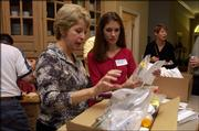 Lisa Buchholz, center, and Becky Hubbell pack medical supplies in preparation for a trip to Romania. Both will travel in early September with a group from the Medical Missionary Foundation to serve as pharmacists for children and families for a week. They are pictured at Hubbell's home in Leawood.