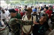 A Louisiana National Guardsmen holds back residents as they gather outside the Louisiana Superdome in New Orleans on Sunday. The Superdome opened Sunday to residents of New Orleans who are seeking shelter from Hurricane Katrina, which is expected to make landfall today.
