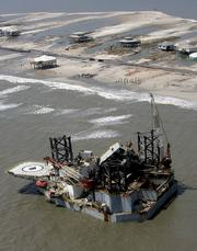 An oil platform, that was ripped Tuesday from its mooring in the Gulf of Mexico, rests by the shore in Dauphin Island, Ala., after hurricane Katrina passed through the area. The potential damage to oil platforms, refineries and pipelines that remain closed along the Gulf Coast drove energy prices to new highs Tuesday, with crude futures briefly topping $70 a barrel and wholesale gasoline costs surging to levels that could lead to $3 a gallon at the pump in some markets.
