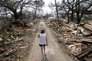 Rhonda Braden walks through the destruction in her childhood neighborhood Wednesday in Long Beach, Miss. Hurricane Katrina destroyed the area where her father lived.