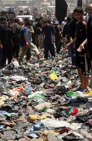Shoes and other belongings of the victims are seen on a bridge over the Tigris river in Baghdad, Iraq. A railing collapsed Wednesday on the bridge packed with Shiite worshippers marching in a religious procession, sending crowds tumbling into the Tigris River. At least 840 people died.