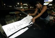 Hurricane Katrina evacuee Ronda Caldoron, 35, from New Orleans, adjusts some signs on her car in a parking lot across the street from Reliant Stadium and the Astrodome in Houston. Caldoron was turned away from staying at the Astrodome, which will house only people who were stranded at the dank, sweltering Superdome in New Orleans, where the water was rising, the air conditioning was out and toilets were broken.