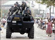 A SWAT team drives past flood victims Thursday waiting at the convention center in New Orleans. Officials are trying to curb the growing lawlessness in New Orleans in the wake of Hurricane Katrina.