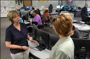 Douglas County Emergency Management Director Paula Phillips, left, says officials need to revisit emergency plans in light of the lessons of Hurricane Katrina. Phillips talked with Dagna D'Ercole, emergency communications center training coordinator, Friday at the center.