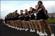 Lawrence High cheerleaders sing their school's alma mater before kickoff against Leavenworth High on Friday at Haskell Stadium.