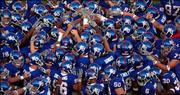 A sea of helmets converge at the center of Memorial Stadium as the Jayhawks huddle up before kickoff Saturday against Florida Atlantic.