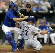 Texas' Mark Teixeira (23) is tagged out by Kansas City catcher Paul Phillips as umpire Marty Foster looks on. The Rangers won, 5-3, Saturday in Kansas City, Mo.